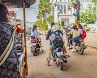 Twee Schoolmeisjes die sidesaddle berijden op hun oudersautoped op manierhuis van school, Naad oogsten Kambodja stock foto's