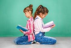 Twee schoolmeisjes gelezen boeken Het concept kinderjaren, het leren Stock Fotografie
