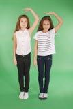 Twee schoolmeisjes houden handen boven hoofd en het meten van zijn groei royalty-vrije stock afbeelding