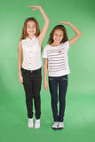 Twee schoolmeisjes houden handen boven hoofd en het meten van zijn groei stock afbeeldingen