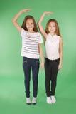 Twee schoolmeisjes houden handen boven hoofd en het meten van zijn groei stock foto