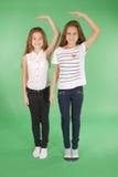 Twee schoolmeisjes houden handen boven hoofd en het meten van zijn groei royalty-vrije stock fotografie