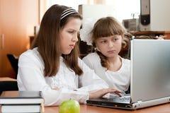 Twee schoolmeisjes voert taak uit gebruikend notitieboekje Stock Foto