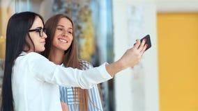 Twee schoonheids vrouwelijke vrienden die sommigen doen die in moderne wandelgalerij winkelen en een selfie met een smartphone ne stock video