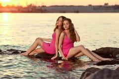 Twee schoonheidsvrouwen op het strand bij zonsondergang. Geniet van aard. Luxegi Stock Foto