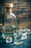 Twee schoten en een fles wodka op houten achtergrond stock foto