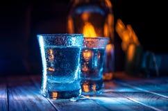 Twee schoten van wodka in de veelvoudige barlichten, close-up stock afbeeldingen