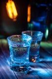 Twee schoten van wodka in de veelvoudige barlichten, close-up stock fotografie