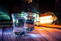 Twee schoten van wodka in de veelvoudige barlichten, close-up royalty-vrije stock fotografie