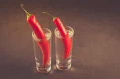 Twee schoten van wodka en Spaanse peper/twee schoten van wodka en Spaanse peper op een donkere achtergrond Selectieve nadruk en c stock foto's