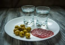 Twee schoten van wodka, olijven en salamiplakken op witte plaat, close-up royalty-vrije stock fotografie