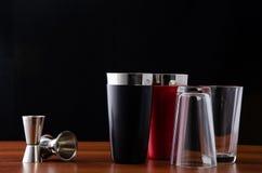 Twee schudbekers van Boston, zwart en rood, en twee jiggers voor het maken van cocktails bij de bar Gedemonteerde schudbeker: gla stock foto's