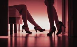 Twee sexy dames in hoge hielen Vrouwen die geslacht hebben Lesbiennes, prostituees of escortes Lang benensilhouet in rood licht royalty-vrije stock fotografie