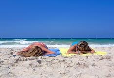 Twee sexy jonge meisjes die op een zonnig strand op vakantie of holi leggen Royalty-vrije Stock Fotografie