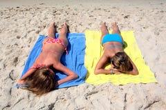 Twee sexy jonge meisjes die op een zonnig strand op vakantie of holi leggen Stock Afbeeldingen