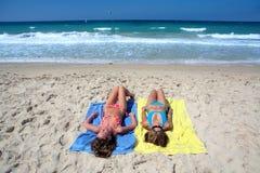 Twee sexy jonge meisjes die op een zonnig strand op vakantie of holi leggen Stock Fotografie