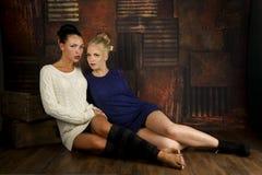 Twee sexy jonge vrouwen in sweater en grunge het plaatsen stock foto's
