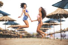 Twee sexy meisjes die op een strand springen Stock Afbeeldingen