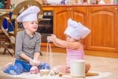 Twee siblings - jongen en meisje - in chef-kok` s hoeden die op de keukenvloer zitten die met bloem wordt bevuild, spelend met vo stock afbeeldingen