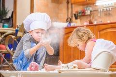 Twee siblings - jongen en meisje - in chef-kok` s hoeden die op de keukenvloer zitten die met bloem wordt bevuild, spelend met vo royalty-vrije stock afbeeldingen