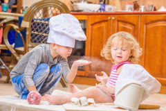 Twee siblings - jongen en meisje - in chef-kok` s hoeden die op de keukenvloer zitten die met bloem wordt bevuild, spelend met vo stock afbeelding