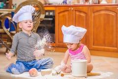 Twee siblings - jongen en meisje - in chef-kok` s hoeden die op de keukenvloer zitten die met bloem wordt bevuild, spelend met vo stock foto's