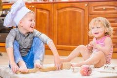 Twee siblings - jongen en meisje - in chef-kok` s hoeden die op de keukenvloer zitten die met bloem wordt bevuild, spelend met vo royalty-vrije stock fotografie