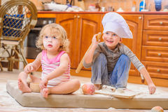 Twee siblings - jongen en meisje - in chef-kok` s hoeden die op de keukenvloer zitten die met bloem wordt bevuild, spelend met vo royalty-vrije stock foto