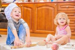 Twee siblings - jongen en meisje - in chef-kok` s hoeden die op de keukenvloer zitten die met bloem wordt bevuild, spelend met vo royalty-vrije stock afbeelding