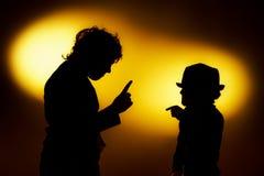 Twee silhouetten die van de expressieve jongen emoties tonen die gesticu gebruiken stock fotografie