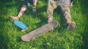twee skateboarders die op een groen gras in een stadspark ontspannen royalty-vrije stock foto