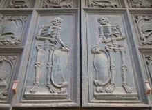 Twee skeletten sneden in hout op de deuren van een oude kerk in Puglia royalty-vrije stock foto's