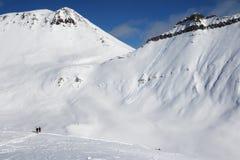 Twee skiërs en off-piste helling met sporen van skis, snowboards a Stock Afbeelding