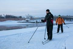 Twee skiërs genieten van de sneeuw en de mening van Volkhov-rivier in Velikiy royalty-vrije stock fotografie