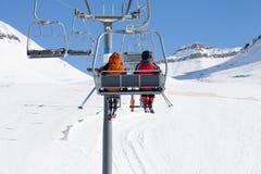 Twee skiërs op stoeltjeslift en sneeuw ski?en helling Royalty-vrije Stock Foto's