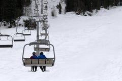 Twee skiërs op stoeltjeslift in grijze dag Stock Afbeeldingen