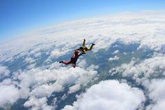 Twee skydivers in kleurenkostuums vallen boven witte wolken stock afbeeldingen