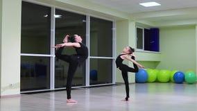 Twee slanke artistieke turners van meisjeszusters in zwarte sportswear do warm-up en voeren oefeningen in ritmische gymnastiek in stock videobeelden