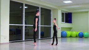 Twee slanke artistieke turners van meisjeszusters in zwarte sportswear do warm-up en voeren oefeningen in ritmische gymnastiek in stock footage