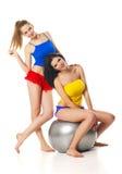 Twee slanke jonge meisjes met geschiktheidsbal Stock Afbeeldingen
