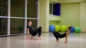 Twee slanke leuke artistieke turners van meisjeszusters in zwarte sportkleding maken opwarming in gymnastiek en voeren spier uitr stock video