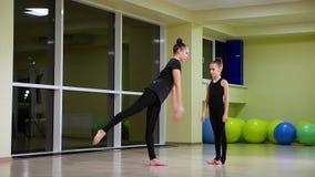 Twee slanke leuke artistieke turners van meisjeszusters in zwarte sportkleding maken opwarming in gymnastiek en voeren spier uitr stock videobeelden