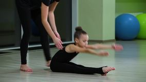 Twee slanke leuke artistieke turners van meisjeszusters in zwarte sportkleding maken opwarming in gymnastiek en voeren spier uitr stock footage