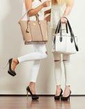 Twee slanke vrouwen binnen met de handtassen van leerzakken Royalty-vrije Stock Foto