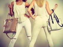 Twee slanke vrouwen binnen met de handtassen van leerzakken Stock Afbeeldingen