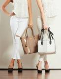 Twee slanke vrouwen binnen met de handtassen van leerzakken Stock Foto's