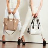 Twee slanke vrouwen binnen met de handtassen van leerzakken Royalty-vrije Stock Fotografie