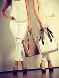 Twee slanke vrouwen binnen met de handtassen van leerzakken Stock Foto