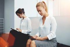 Twee slimme vrouwelijke lezingsinformatie over aanrakingsstootkussen en mobiele telefoon tijdens onderbreking tussen vergadering  Stock Fotografie