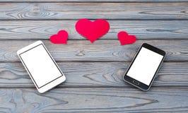 Twee smartphones met cijfers van harten stock foto